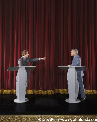 Picture of a debate taking place on a large theater stage with tall red velvet theater curtains as the background. The two politicians are standing at separate podiums or lecterns, and one is pointing at the other with his finger and outstretched arm.